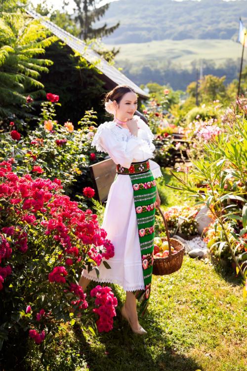 Người đẹp lựa chọn kiểu tóc búi cao kèm theo vài phụ kiện đơn giản như vòng hoa để tôn lên vẻ đẹp của bộ trang phục.