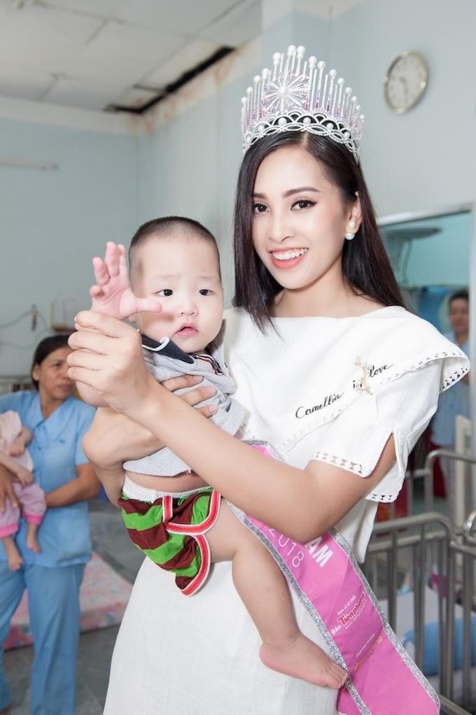 <p> Tiểu Vy âu yếm một em bé trên tay.</p>