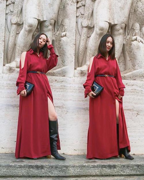 Nữ ca sĩ mặc bộ váy đỏ có thiết kế khoét vai xẻ tà và phối cùng những item màu đen như thắt lưng, boot, ví cầm tay...