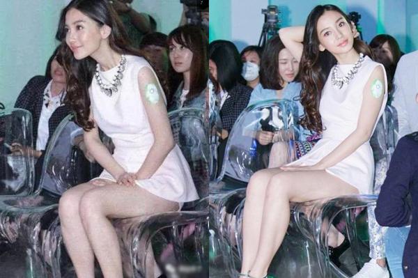 Chiếc váy quá ngắn khiến Angelababy khổ sở khi ngồi, hai tay cố gắng đè chặt vạt váy.