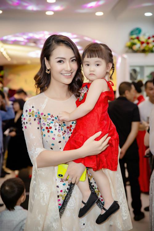 Người mẫu Hồng Quế gây chú ý khi diện áo dài đính kim sa lấp lánh và bế theo cô con gái đáng yêu. Kể từ khi con gái cứng cáp, Hồng Quế thường xuyên cho bé đi dự sự kiện cùng để chia sẻ niềm đam mê thời trang với mẹ.