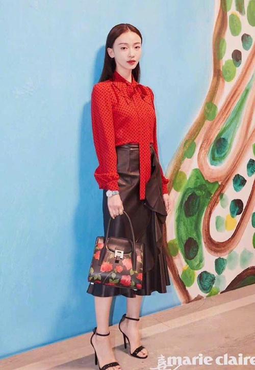 Tại show Michael Kors, cô diện set đồ thanh lịch với áo sơmi đỏ họa tiết chấm bi mix cùng chân váy da, tóc buông xõa nữ tính.