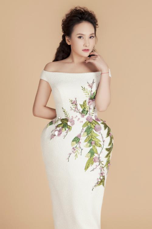 Tông màu trắng nền nã mang đến vẻ sang trọng được nhất nhá bởi hoạ tiết 3D đính ở thân váy. Đầm trễ vai khéo khoe vẻ quyến rũ và nữ tính của người mặc.
