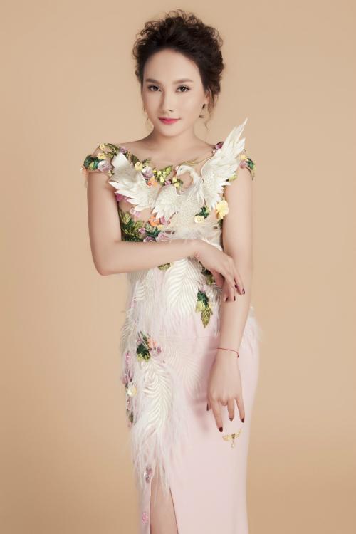 Thân trên của trang phục được kết đính cầu kỳ với hoạ tiết chim phụng và hoa 3D. Gam màu trắng và hồng pastel của trang phục làm nổi bật họa tiết.