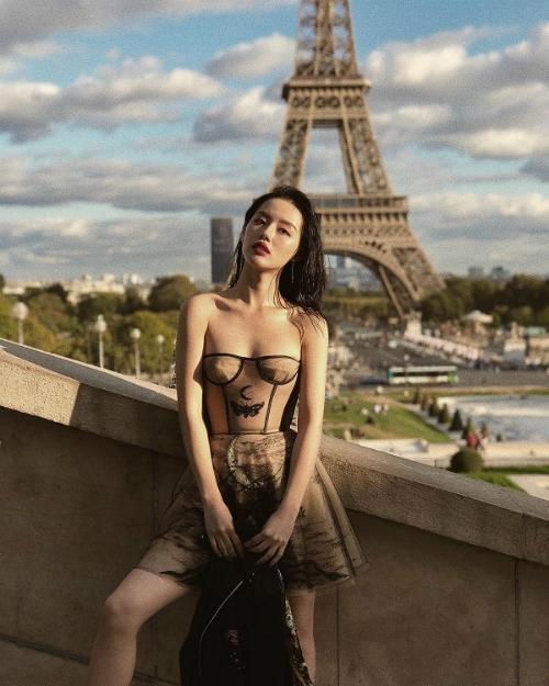 Có mặt trên đất Pháp để tham dự Paris Fashion Week, Khánh Linh The Face đụng váy với Phạm Hương. Tuy nhiên, kiểu tóc hất ngược về phía sau giúp nữ hoàng lookbook khoe trọn ngực đầy cùng xương quai xanh gợi cảm.