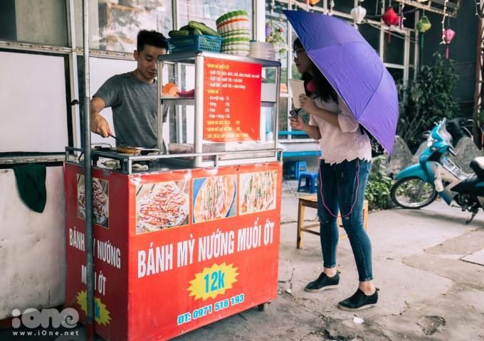 """<p> Bánh mì nướng muối ớt là món ăn của người dân Khmer, phổ biến ở thành phố Long Xuyên, An Giang sau này lan dần sang các vùng miền khác. Khi đến Sài Gòn, món ăn đã tạo thành một """"cơn sốt"""", thu hút giới trẻ vì lạ miệng, dễ tìm và giá cả hợp lý.Giờ đây bánh mì nướng muối ớt cũng trở thành món ăn vặt quen thuộc với giới trẻ Hà Nội.</p>"""