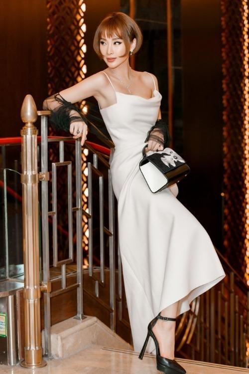 Diện bộ váy tương tự HHen Niê, Angela Phương Trinh cũng chọn vòng cổ ngọc tai làm điểm nhấn. Cô chọn giày cao gót quai ngang và túi xách tone đen, điểm xuyết tổng thể. So với HHen Niê, bà mẹ nhí quyến rũ, sành điệu hơn hẳn nhờ chọn đúng kiểu tóc bum bê, hợp khuôn mặt.