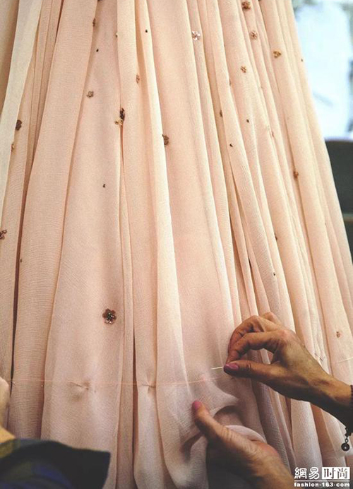 Các nghệ nhân đã mất khoảng 1.250 giờ để thực hiện tất cả các công đoạn bằng tay, bao gồm đính cườm, thêu hoa 3D khắp thân váy, cổ và eo được đính pha lê.