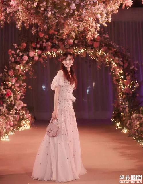 Ngoài bộ váy cưới trắng muốt lộng lẫy, trong hôn lễ, Đường Yên còn khoác lên mình nhiều bộ váy cưới đặc biệt khác. Thiết kế màu vàng mơ cô diện khi chào khách cũng kỳ công không kém. Kiểu dángtrễ vai đắp diềm bèo mang đến cảm giác lãng mạn và hoài cổ.