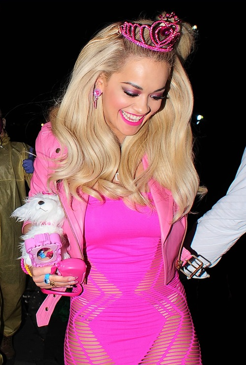 Rita Ora tỏa sáng trong tiệc Halloween tại London năm 2014 khi đội vương miện Barbie và diện nguyên cây màu hồng trứ danh của nhân vật búp bê huyền thoại. Cô nàng thậm chí còn mang thêm những phụ kiện như cún bông, gương... để hoàn thiện set đồ theo chủ đề Barbie.