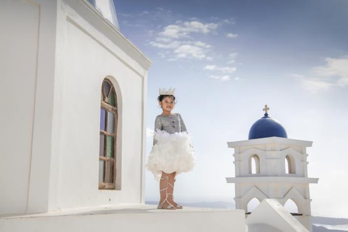 """<p> Kathy đội vương miện, tạo dáng ở Blue Dome - nơi nổi tiếng nhất của Santorini, Hy Lạp. Chiếc đầm trắng thiên thần """"Angel of Peace"""" do mẹ bé thiết kế.</p>"""