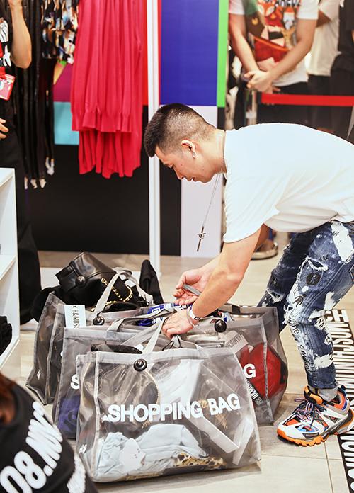 Stylist Travis Nguyễn tay xách nách mang cả chục món đồ, quét sạch các kệ để hàng.