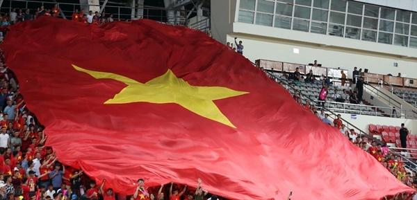 CĐVViệt Nam đem cờ đại cổ vũ tuyển Việt Nam trên sân Lào.Ảnh: Đức Đồng.