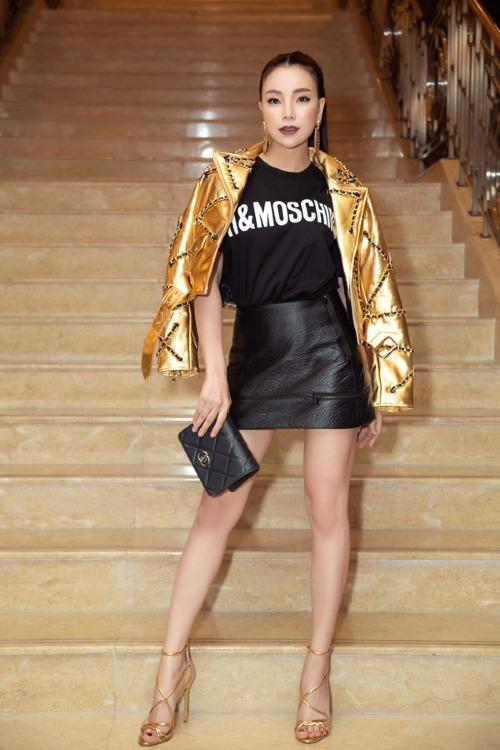 Trà Ngọc Hằng diện cây đồ mới nhất của Moschino X H&M. Để hoàn thiện thêm cho set đồ gồm áo thun mix cùng chân váy da, giày cao gót quai ngang và ví Chanel, người đẹp dòm ngực khoác hờ hững áo ánh kim, tạo điểm nhấn phong cách.