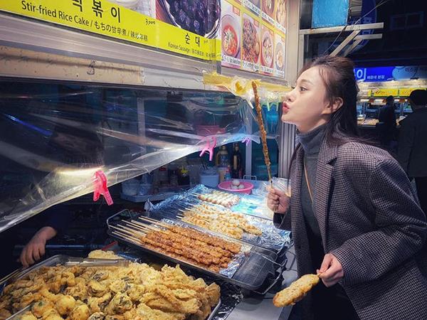 Phương Oanh nhí nhảnh ăn thịt nướng ven đường trong chuyến công tác Hàn Quốc.