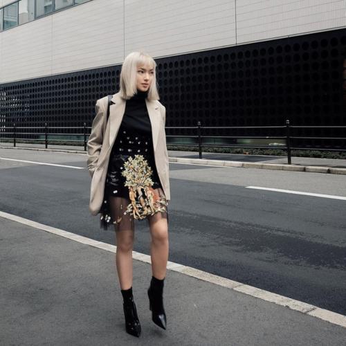 Cùng diện váy tương tự Thùy Trang nhưng Châu Bùi lại chọn cách mix đồ kín đáo hơn. Với thời tiết lạnh tại Nhật, bạn gái Decao phối váy hai dây cùng áo cổ lộ giữ ấm và áo khoác ngoài. Cô nàng cũng lựa chọn boots cổ cao tiệp màu đen để ăn gian chiều cao.