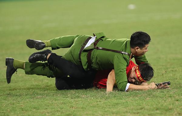 Cuộc vật lộn giữa một cảnh sát và fan cuồng trên sân cỏ.