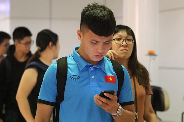 Quang Hải vừa đi vừa nhắn tin điện thọai.