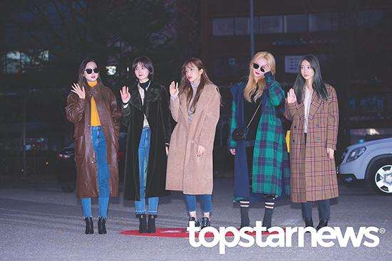 EXID mặc đồng phục trench coat dáng dài khi đến Music Bank. Chị cả Sol Ji luôn phải đeo kính đen vì căn bệnh ở tuyến giáp.