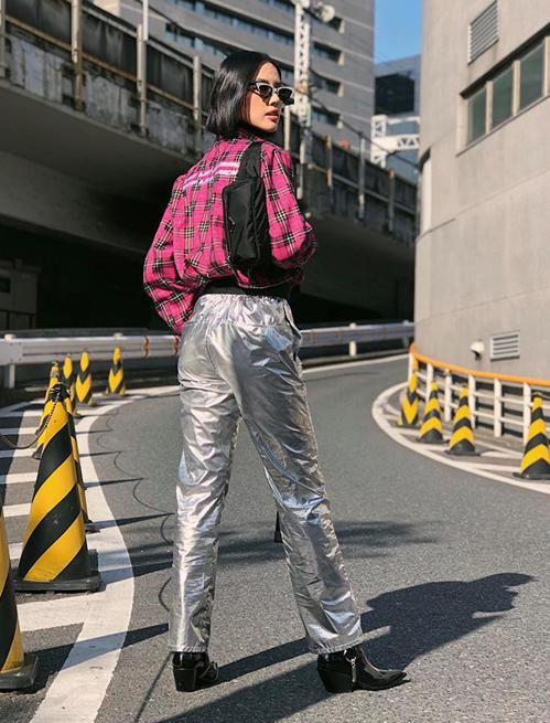 Khánh Linh là mỹ nhân hiếm hoi có thể chinh phục kiểu quần bóng loáng chẳng khác gì... quần đi mưa. Cô nàng còn kết hợp cùng sơ mi hồng nổi không kém.