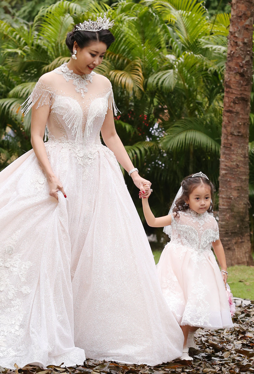 Trong bộ trang phục công chúa lộng lẫy, Hoa hậu Việt Nam 1992 đội vương miện, nắm tay con gái út catwalk cùng hai con trai.