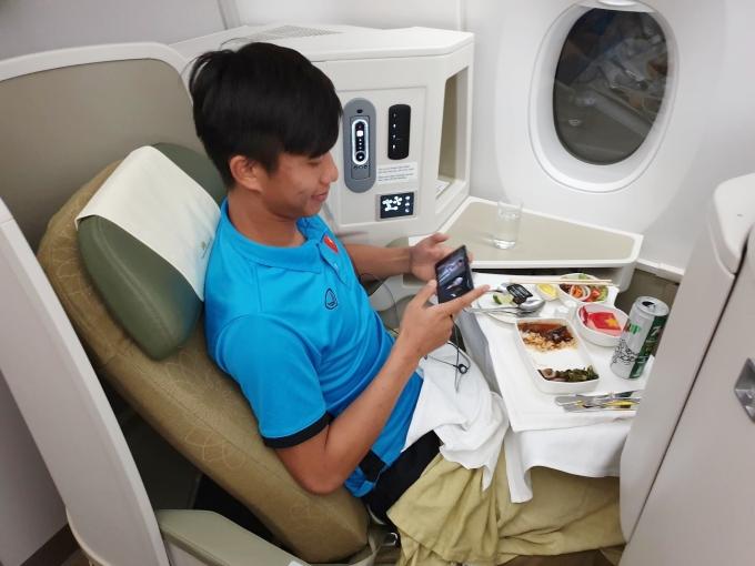 """Tranh thủ thời gian, các cầu thủ """"cày phim"""" thư giãn trên máy bay. Văn Đức """"cắm mặt"""" vào điện thoại sau khi dùng bữa trên máy bay."""