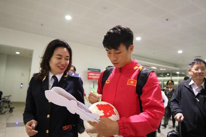 <p> Bùi Tiến Dũng thân thiện ký tặng một nhân viên ở sân bay.</p>
