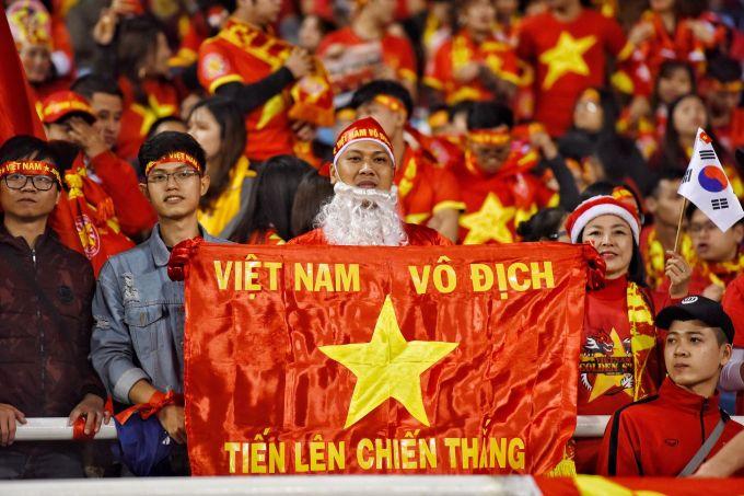 """Một CĐV hóa thành ông già Noel trên khán đài với dòng chữ trên lá cờ: """"Việt Nam vô địch - Tiến lên chiến thắng""""."""