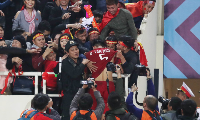 <p> Chiến thắng 1-0 trên sân nhà Mỹ Đình không chỉ giúp đội tuyển Việt Nam lên ngôi vô địch AFF Cup 2018 mà còn phá vỡ kỷ lục, khi vượt Pháp, trở thành đội tuyển quốc gia có chuỗi trận bất bại lớn nhất thế giới (16 trận). Thành tích này khiến các cầu thủ vui sướng, xúc động. Trong hình, Đoàn Văn Hậu vượt vòng vây phóng viên để nhảy ào lên khán đài, ăn mừng chiến thắng cùng mẹ.</p>