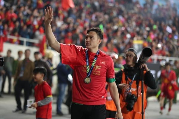 Văn Lâm đeo huy chương chào khán giả sau trận đấu tối 15/12.