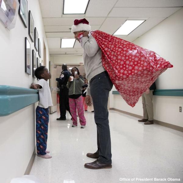 Ông già Noel Obama với chiếc túi khệ nệ đi phát quà cho bệnh nhi.