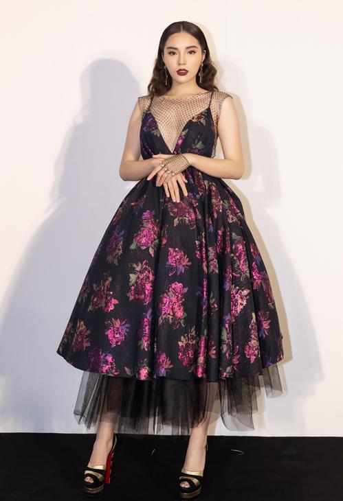 Hoa hậu Việt Nam 2014 - Kỳ Duyên chọn thiết kế dáng xoè, xẻ ngực sâu gợi cảm. Trên nền đen, hoạ tiết hoa với sắc hồng được tôn lên tuyệt đối. Người đẹp 9X tạo nên sự cầu kỳ với áo lưới, găng tay lưới cùng giày kẻ sọc của Christian Louboutin.