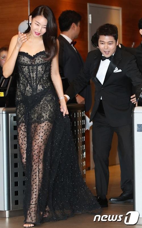 Người mẫu Han Hye Jin trở thành tâm điểm với chiếc váy xuyên thấu, lộ thân hình nóng bỏng. Chuyện tình lệch chiều cao giữa siêu mẫu và nam MC Jeong Hyun Moo (người đi sau) khiến công chúng thích thú.
