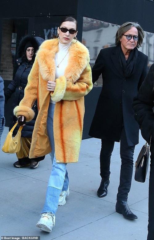 Bella diện trang phục sành điệu với áo khoác lông màu cam nổi bật phối cùng áo thun cổ lọ màu trắng và quần jeans ống suông.