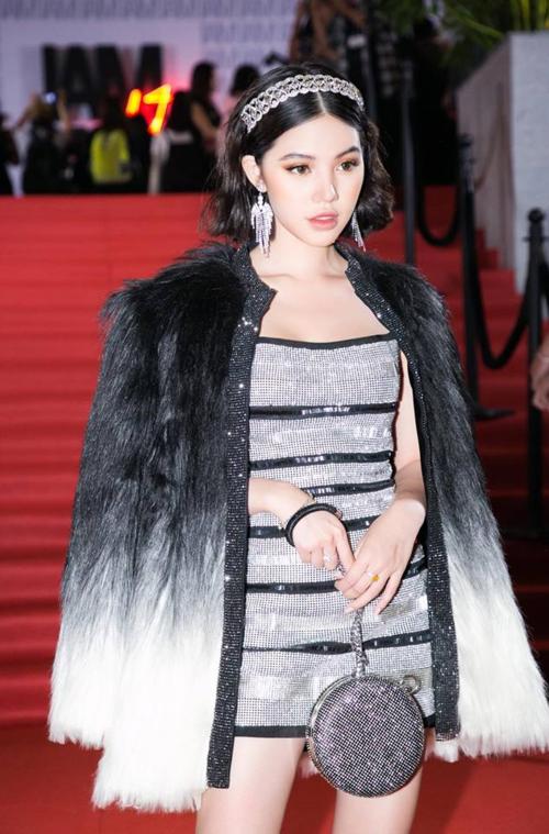 Thiết kế mà Phí Phương Anh diện của NTK Chung Thanh Phong từng được Jolie Nguyễn diện trong một sự kiện hồi tháng 11 năm ngoái. Hoa hậu Việt Nam tại Úc mix item này cùng túi lựu đạn của Yves Saint Laurent, áo khoác lông cùng phụ kiện vương miện, bông tai đắt giá.