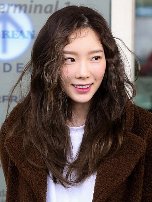 Tae Yeon lựa chọn phong cách thoải mái, năng động tại sân bay gồm áo khoác lông dáng dài, áo thun trắng và boot đen. Ngoài giọng hát đã quá nổi tiếng, thủ lĩnh SNSD luôn khiến người hâm mộ phải xuýt xoa trước vẻ đẹpkhông tuổi, đặc biệt là làn dacăng bóng.