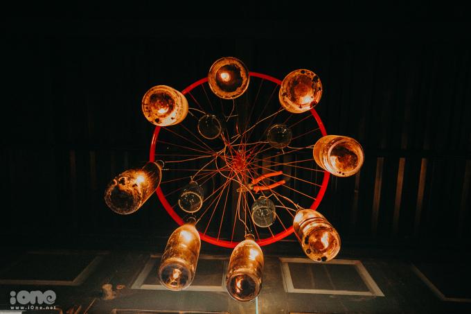 <p> Những vỏ chai rượu cũ kết hợp với vành bánh xe bỏ đi tạo thành những chiếc đèn trần độc đáo.</p>