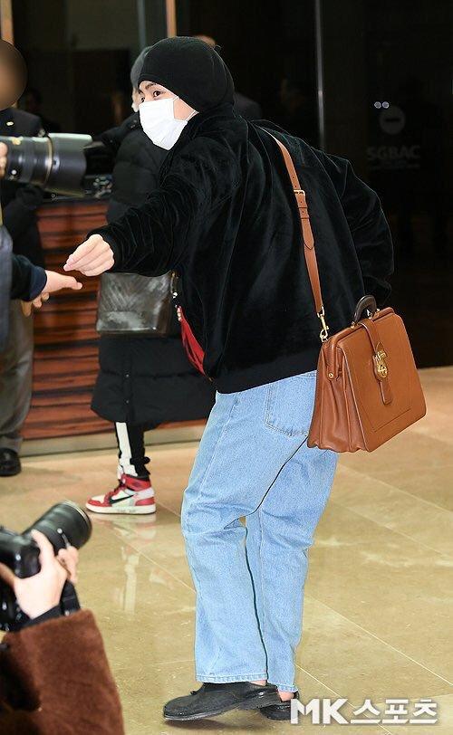 Vluôn có style khác biệt. Anh chàng diện áo Gucci, túi Burberry sành điệu. Hành động bắt tay nhà báo của V khiến các fan thích thú.