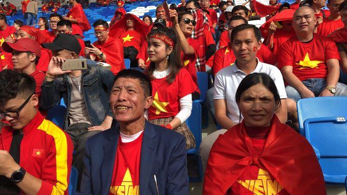 <p> Bố mẹ cầu thủ Đoàn Văn Hậu cùng mặc đồng phục áo cờ đỏ sao vàng, háo hức chờ màn thể hiện của con trên sân cỏ. Anh trai Quang Hải mặc áo trắng, phía trên.</p>