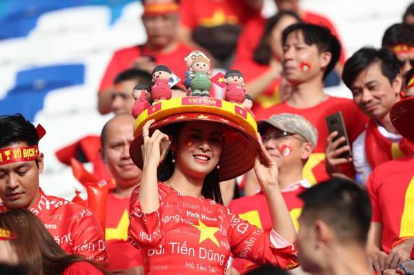 Ngọc Hân mặc áo dài đỏ Việt có in tên các cầu thủ, cô đội nón lá kèm những bức tượng nhí nhảnh mô phỏng các tuyển thủ của Việt Nam.