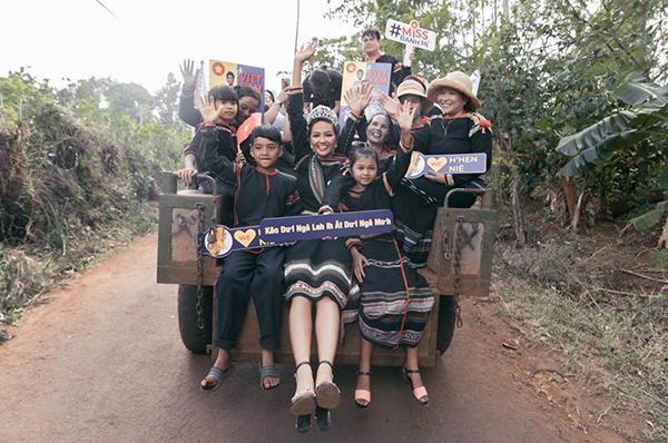 Trong chuyến về thăm quê lần đầu sau khi vào Top 5 Miss Universe, HHen Niê mặc váy thổ cẩm, trên tay là tấm bảng in câu nói của người Ê đê, rạng rỡ ngồi công nông vào chào buôn làng.