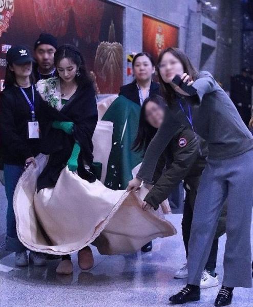 Đi tập duyệt chương trình mừng năm mới, Dương Mịch cũng chỉ mặc váy, đi giày cao gót khi đứng trên sân khấu. Rời khỏi khán phòng là cô nàng có ngay đội ngũ nhân viên choàng áo, đổi dép bông vừa ấm áp vừa thoải mái.