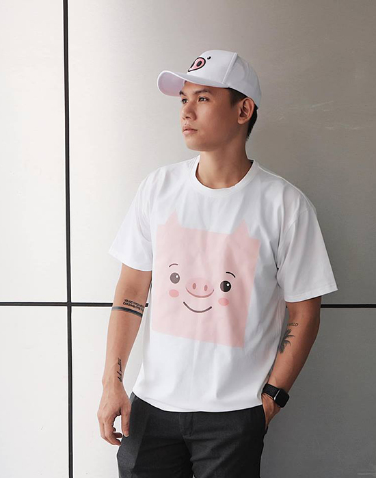 """<p> Đại Nhân mix áo phông trắng in hình heo hồng đáng yêu cùng quần thô đen và mũ lưỡi trai. Họa tiết heo con theo phong cách pop art được NTK Hà Nhật Tiến tung ra vào thời điểm cuối năm gây nên """"cơn sốt"""" trên thị trường.</p>"""