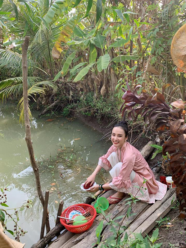 """<p> Mùng 2 Tết Âm lịch, Angela Phương Trinh khoe ảnh cùng em gái và mẹ về quê nội ăn Tết. Mặc áo dài truyền thống nhưng """"bà mẹ nhí"""" không ngại ngồi xổm, đi dép tông và ngồi rửa bát bên cạnh ao.<br /></p>"""