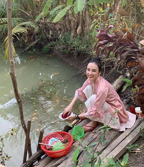 Angela Phương Trinh ngồi rửa bát ở bờ ao khi về quê.