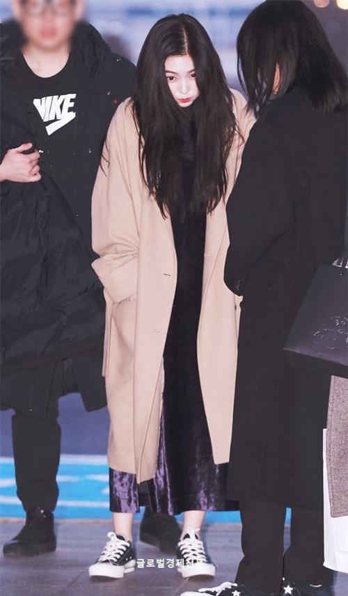 Irene giữ ấm với áo khoác dạ, váy liền dễ di chuyển. Trưởng nhóm có biểu cảm đáng yêu khi bị gió thổi ở sân bay.