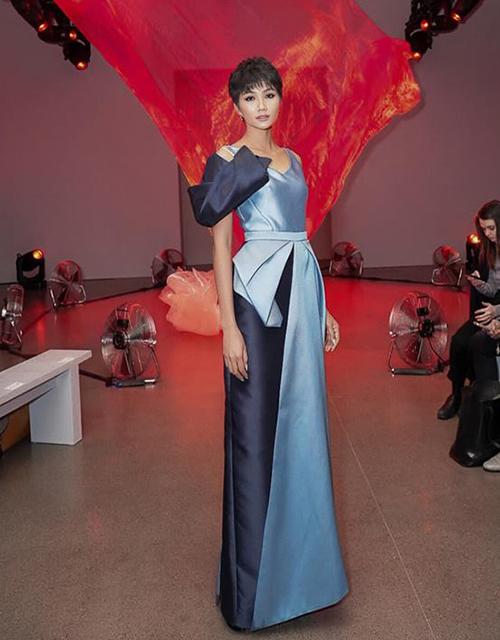 HHen Niê diện một thiết kế của Phương My với tông xanh làm chủ đạo. Thời tiết New York đang xuống dưới 0 độ với tuyết rơi dày đặc nhưng Hoa hậu Hoàn vũ Việt Nam 2017 vẫn bất chấp mặc đồkhông tay. Sau khi rời show, cô lập tức phải mặc ngay áo phao để giữ ấm.