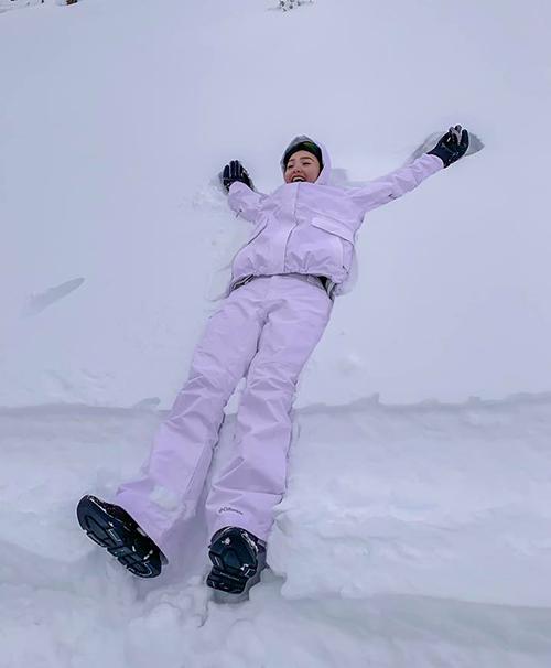 Minh Hằng bất chấp việc có thể dính cảm vẫn phải thử cảm giác được nằm trên lớp tuyết trắng dày.