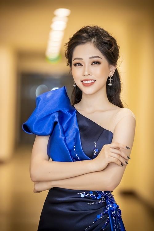 [Cô xuất hiện với chiếc đầm dạ hội màu xanh bắt mắt, khoe làn da trắng và nụ cười rạng rỡ.