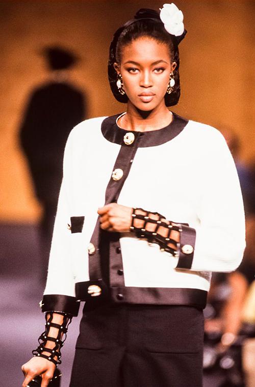 Kiểuáo khoác hình vuông với đường viền to và những chiếc khuy đính nổi bật cho đến nay vẫn được ưa chuộng. Lagerfeld đã giúp mẫu áo này trở thành thiết kế kinh điển của hãng, chỉ cần nhìn là nhận ra Chanel. Phom dáng từ BST Thu Đông 1989 mà Naomi Campbell diện gần như vẫn được giữ nguyên qua hàng chục năm.